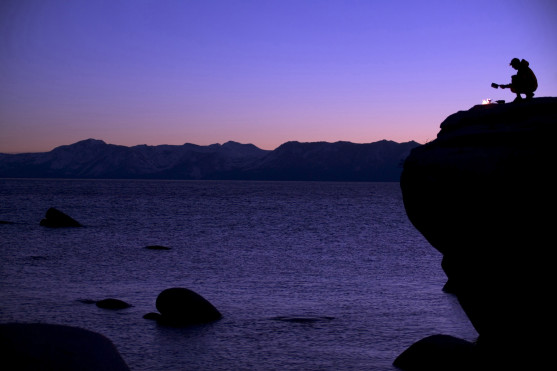 Silhouette of a hiker crouching at the edge of a rock